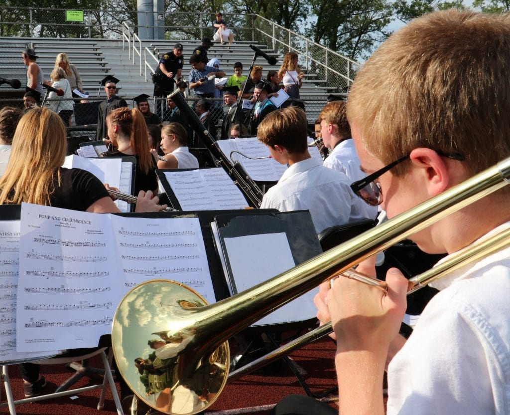Band students perform outside bleachers. Music says Pomp and Circumstance.
