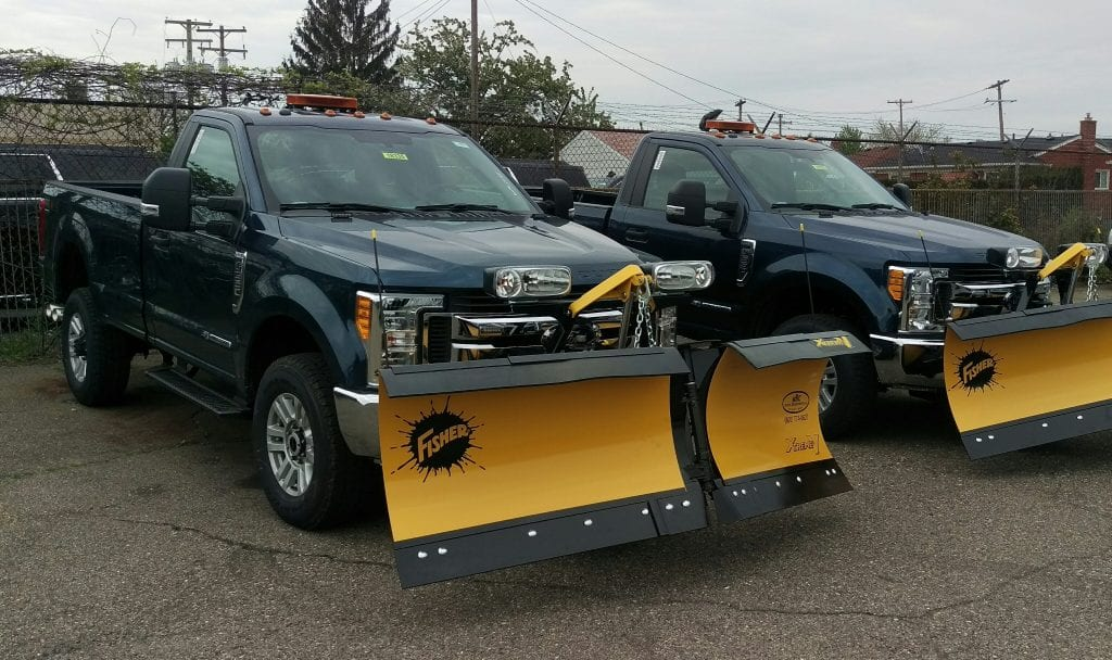 Two pickups equipped with snow plows.