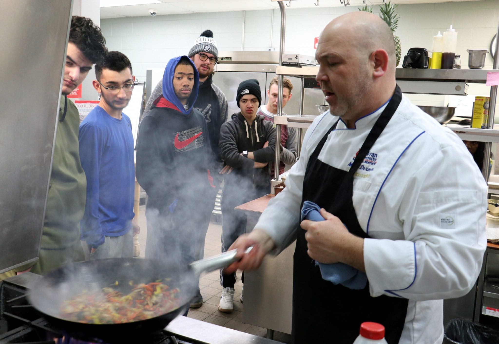 A chef shakes a skillet while six students watch at the Michael Berry Career Center.