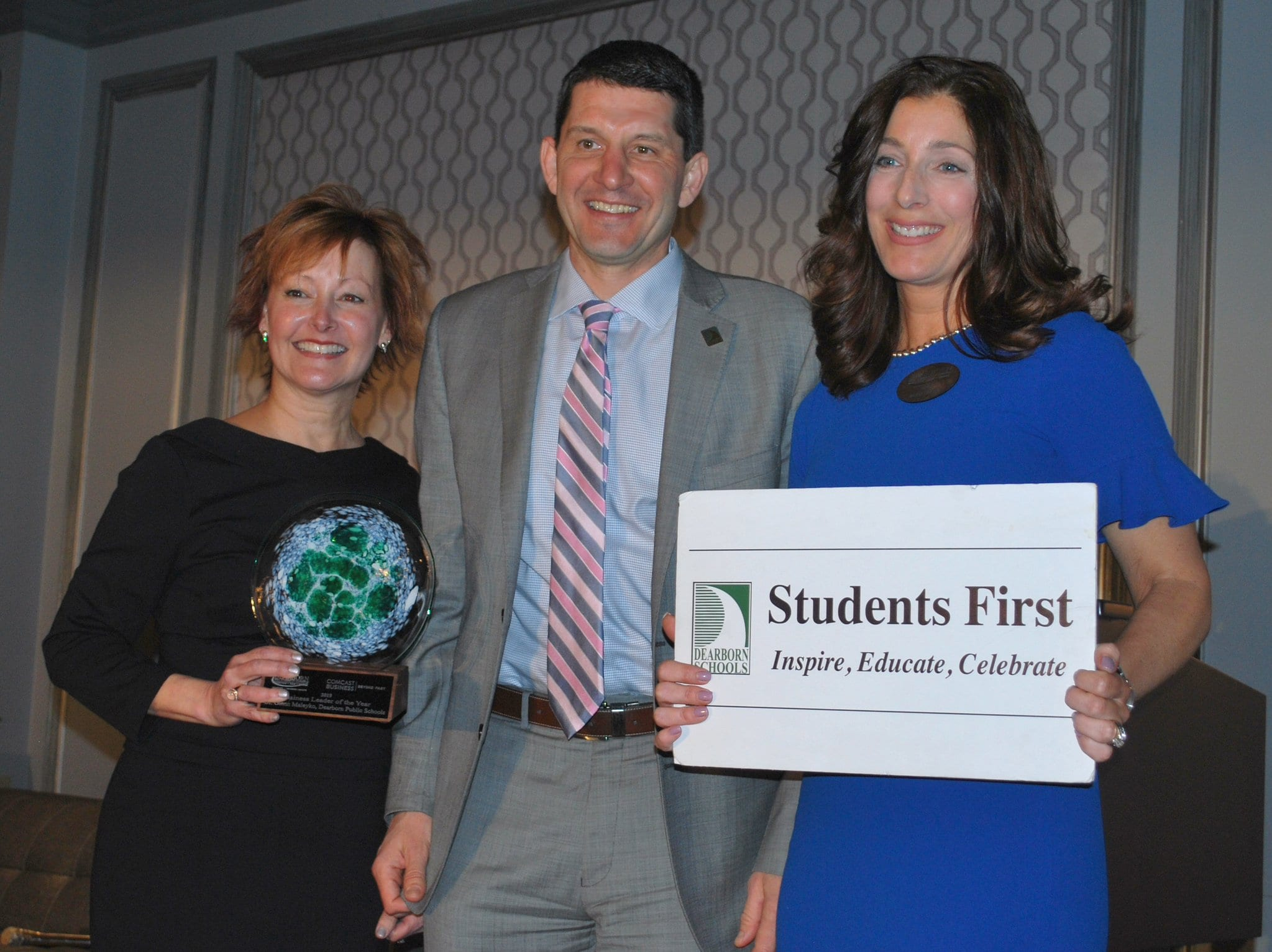 Chamber President Jackie Lovejoy, Dearborn Schools Superintendent Glenn Maleyko and Chamber Board of Directors Chair Maria Fracassa Dwyer pose with the Business Leader of the Year Award and Dearborn Schools Students First sign.