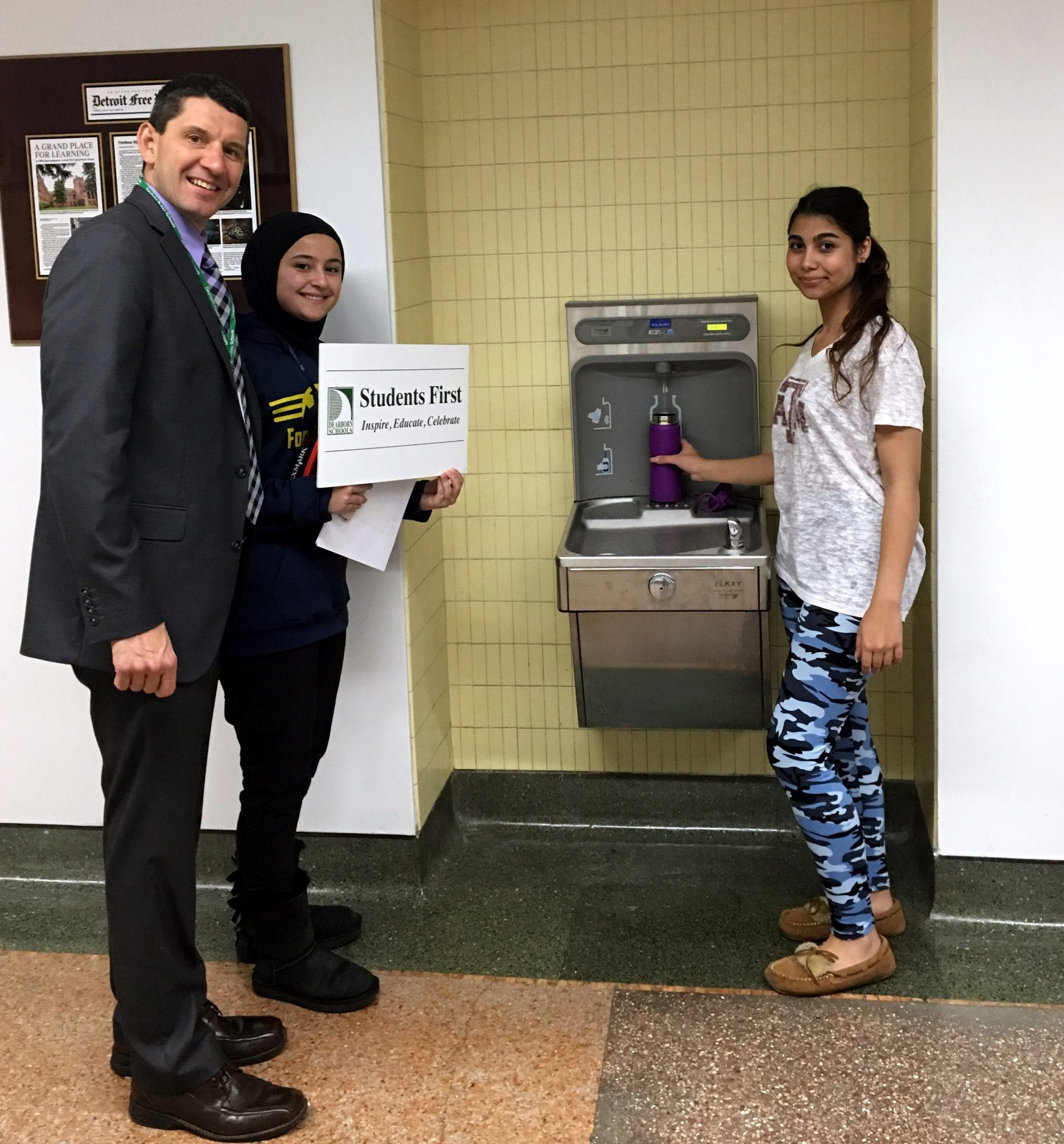 Superintendent Glenn Maleyko poses with two students by a new hydration station at Fordson High School.