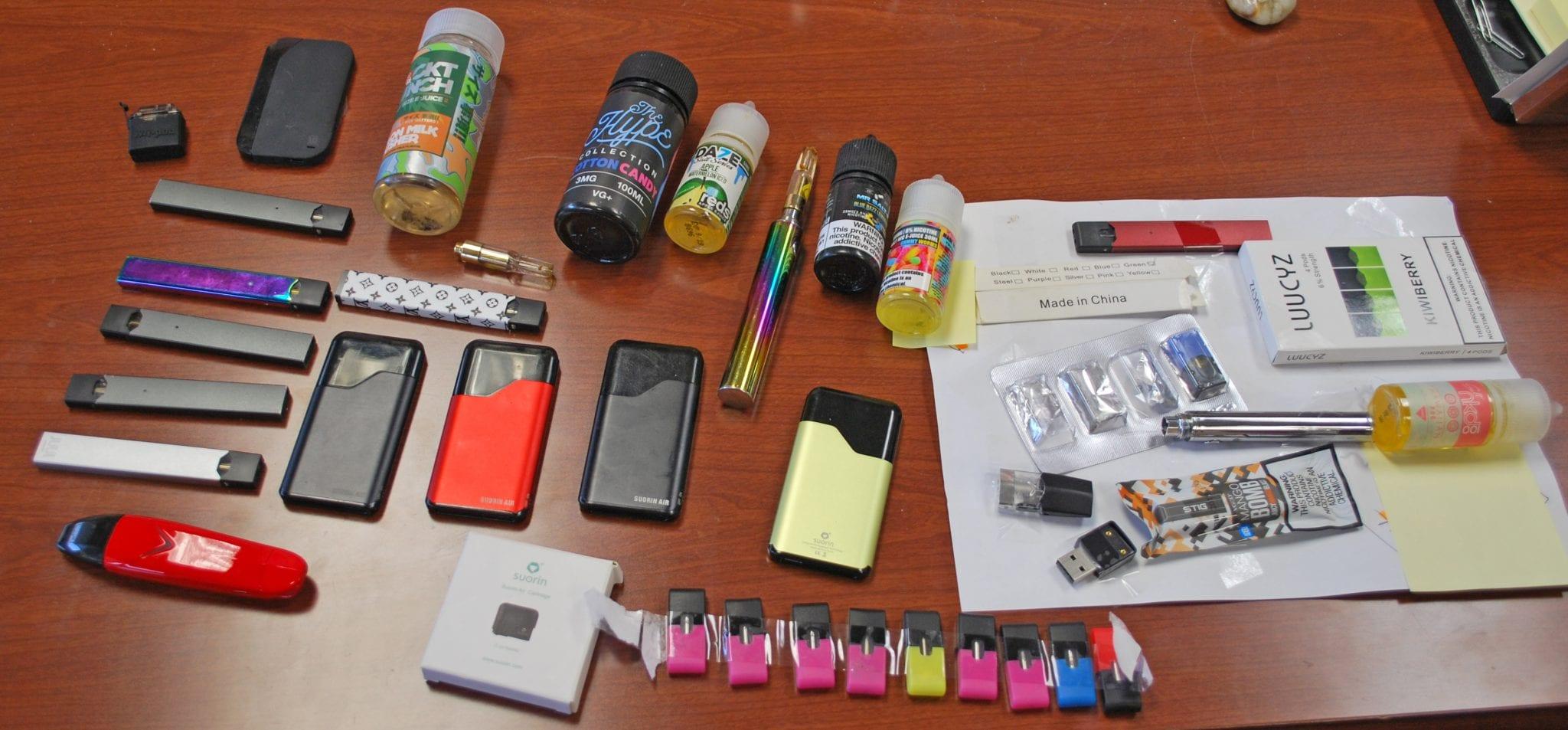 A couple dozen vaping devices are shown on a desk.