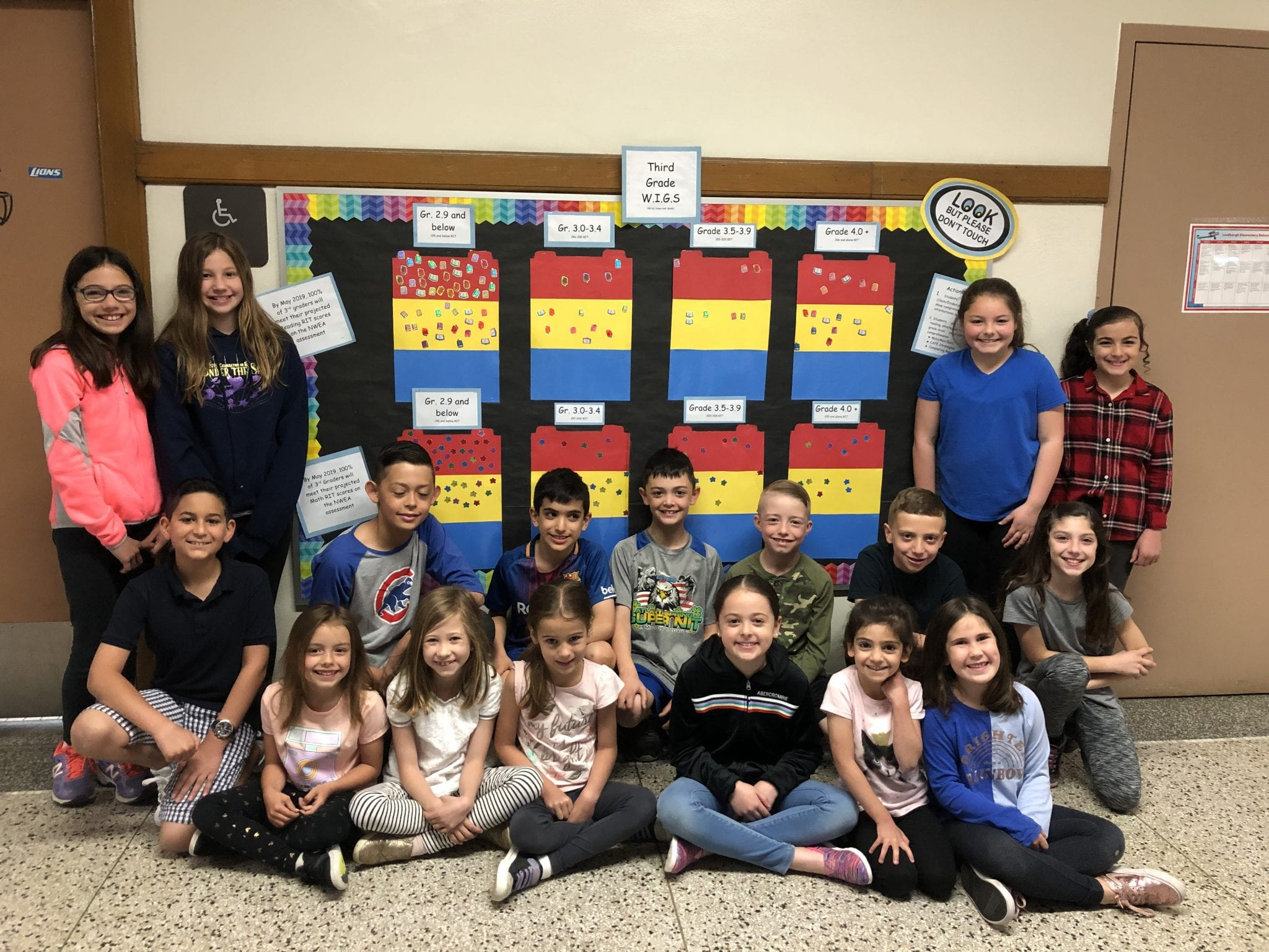 Students pose around a colorful bulletin board
