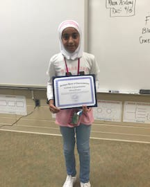 Student Afnan Hassan poses with a certificate she received for participating in Fuel Up to Play 60.