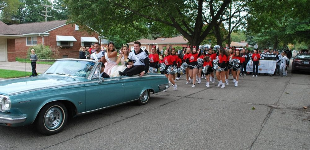 Members of the Homecoming court ride in a convertible while cheerleaders follow during the 2018 Edsel Ford High School Homecoming parade.