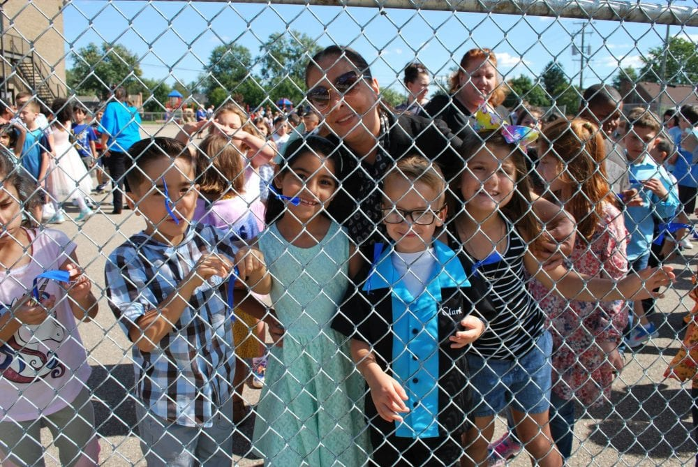 Students and an adult peer through the fence outside Lindbergh Elementary school on Sept. 26, 2019. Small blue ribbons are tied to the fence.