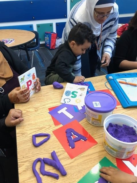A young child and adults shape purple play dough in the shape of letters printed on paper.