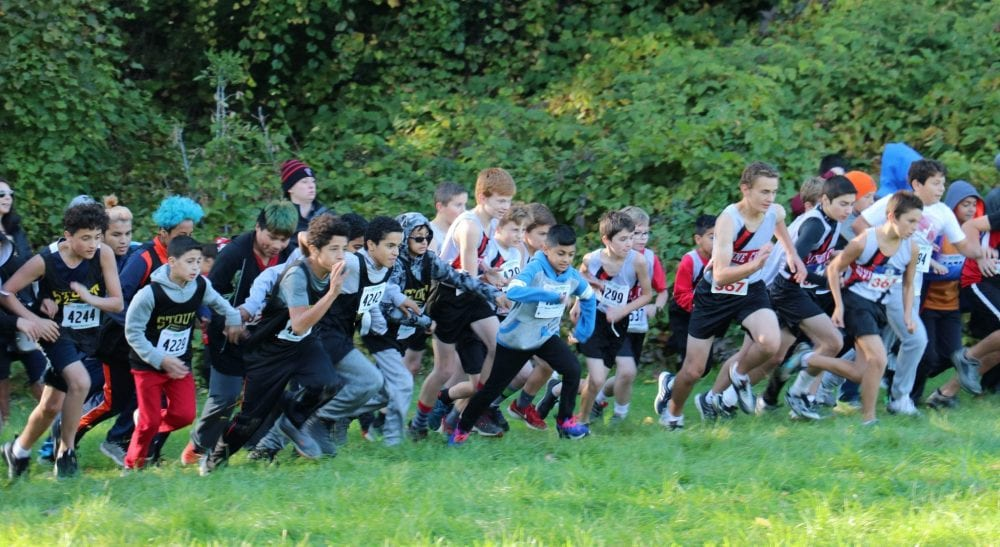 Dozens of middle school boys lunge forward a the start of the 2018 Cipriano Run.