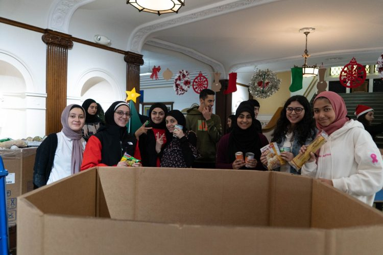 Several Fordson High School students pose with food donations as they count and pack donations.