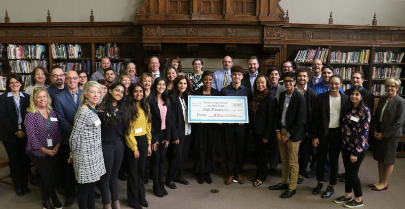 A large group of adults and high school students gather in the Fordson High media center with an oversized check for $5,000 from Macy's to Fordson.