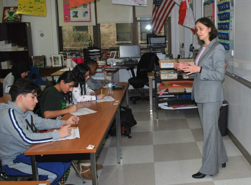 A woman speaks to several students in a classroom during the Fordson Freshman Career Fair.