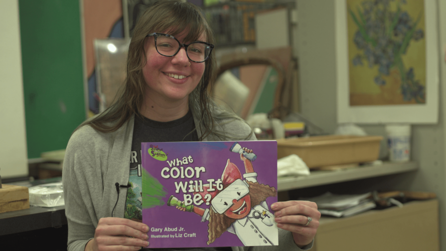 """Liz Donaghue/Craft, an art teacher at Edsel Ford High School, poses with """"What Color Will It Be?"""", the children's book she illustrated."""