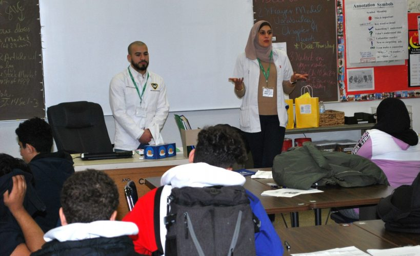 Two pharmacists talk to students during the Fordson High School Career Fair in December 2019.