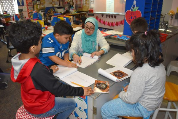 A teacher works on a reading lesson with four elementary students sitting at a table with books and workbooks open.