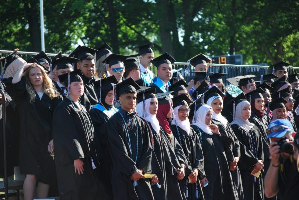Edsel Ford High School students stand on bleachers in their caps and gowns.