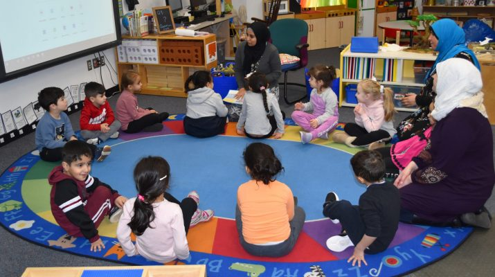 A teacher instructs a group of young students sitting in a circle on the floor.