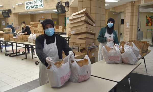 Two women in face masks pack food into bags at McCollough/Unis School.