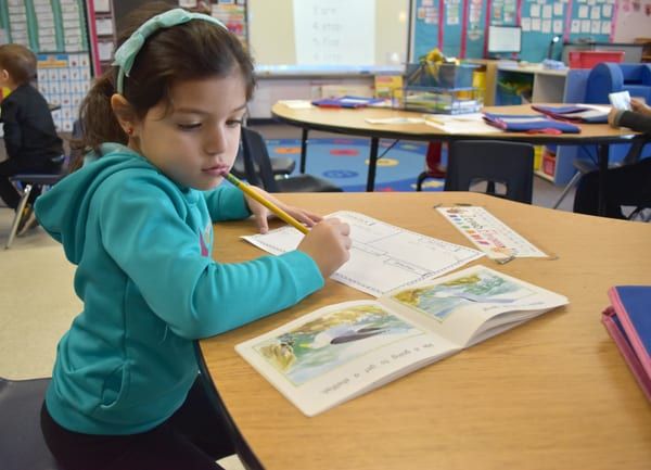 A student looks thoughtful while writing and looking at her reading book.