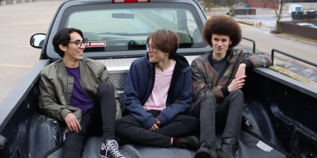 Three teen boys sit in the bed of a pickup in a scene from DHS-student movie Have a Nice Day.