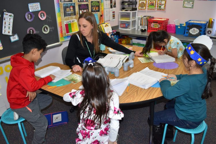 A Dearborn Schools teacher works with four young students gathered around a table.