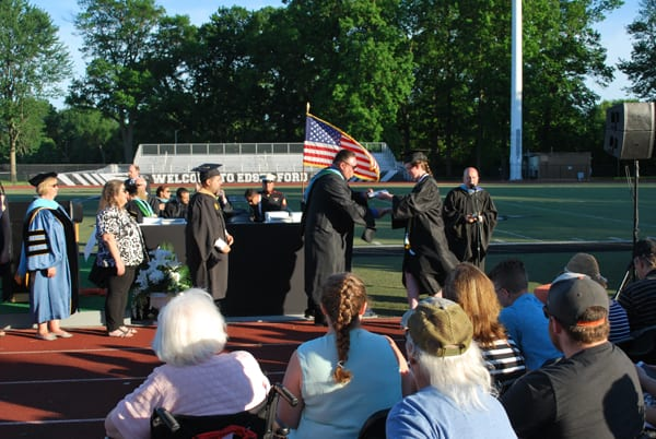 A 2019 Edsel Ford High graduate shakes hands with Principal Scott Casebolt as other dignitaries look on during graduation.
