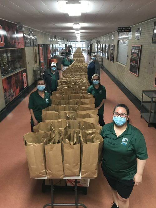 District staff stand by hundreds of bags of food they packed before Memorial Day weekend.