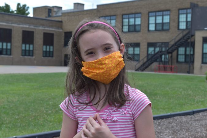 A girls poses in a face mask outside an elementary school.