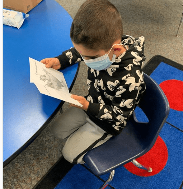 A boy in a face mask reads during a learning lab at Henry Ford Elementary.