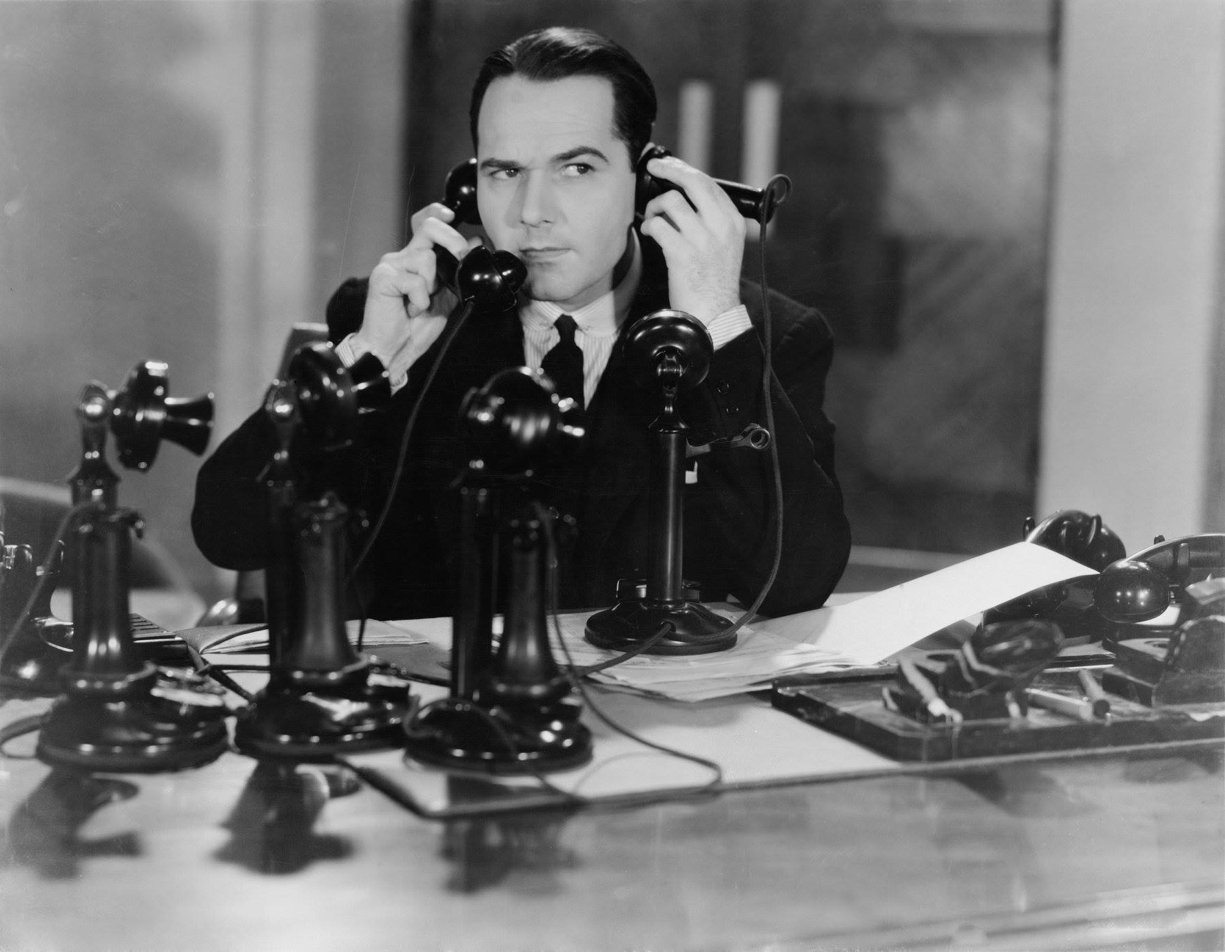 In a black and white photo a man tries to talk on several old fashioned phones.