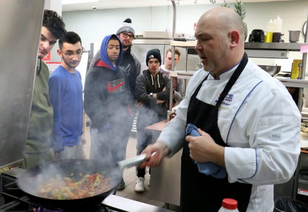 A hospitality teacher shows students how to cook a meal on the stove while students watch at Michael Berry Career Center.