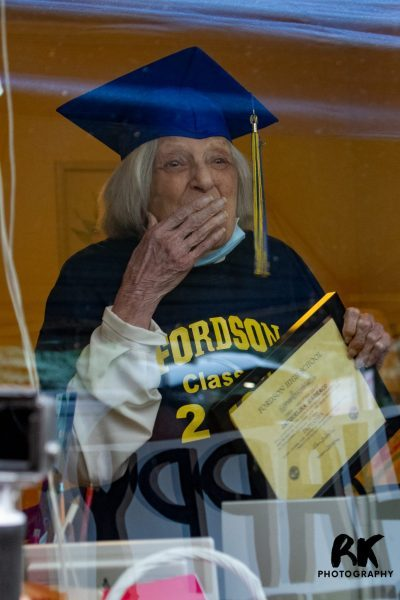 Jacquelina Barraco holds her honorary Fordson diploma while wearing a graduation cap and tassel on her 100th birthday on Nov. 25, 2020. She is at a window in her home reacting to family members offering their well wishes outside her window.
