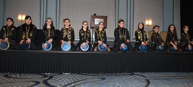 Eleven students from Maples Elementary sit on the front edge of a stage playing drums.
