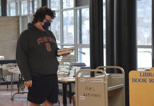 A Dearborn High School student picks up books in the school library in March.