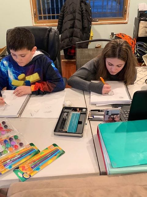 Two students work with art supplies at a table at their home.
