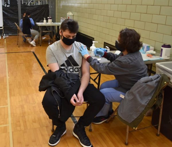 A male student gets vaccinated by a nurse at an April clinic at Edsel Ford High School.