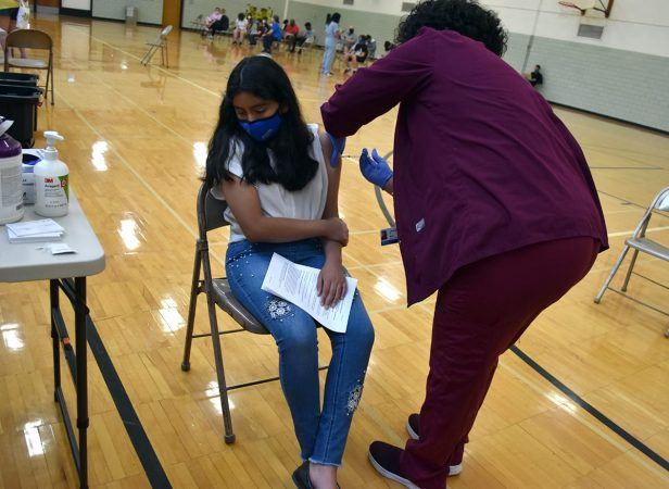A girl turns her head while a nurse administers a COVID vaccine in May at Edsel Ford High School.