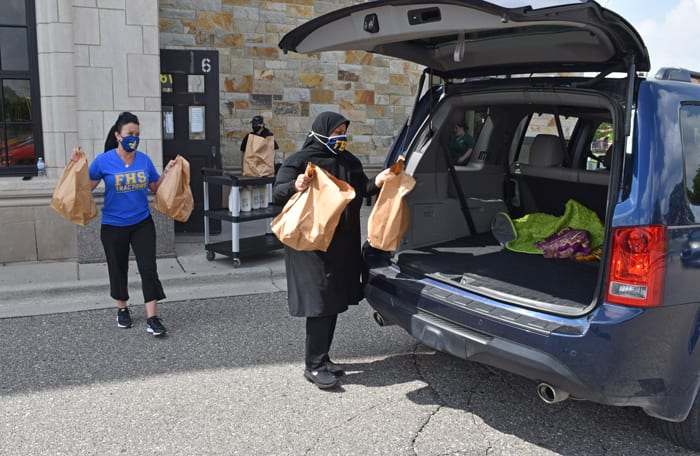 Two workers load bags of food and milk into a vehicle's trunk during a weekly student meal distribution at Fordson High School on June 9, 2021.