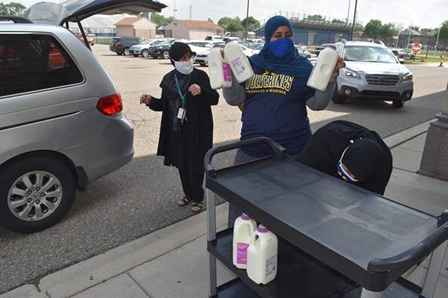 Two women load milk and bags of food into a mini van outside Fordson High School in June.