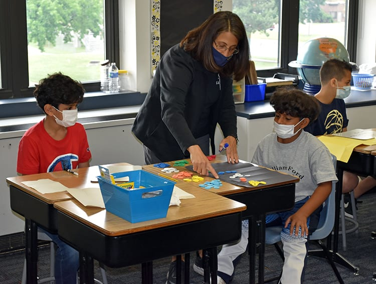 A teacher at William Ford Elementary helps students with a lesson on place values during the first day of the district's Summer Academic and Enrichment Program on Wednesday, June 23. The district is using federal COVID relief funding to pay for the summer program.
