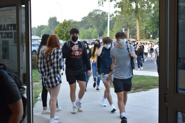A group of students in masks walks into Dearborn High on the first day of school, Aug. 30, 2021.