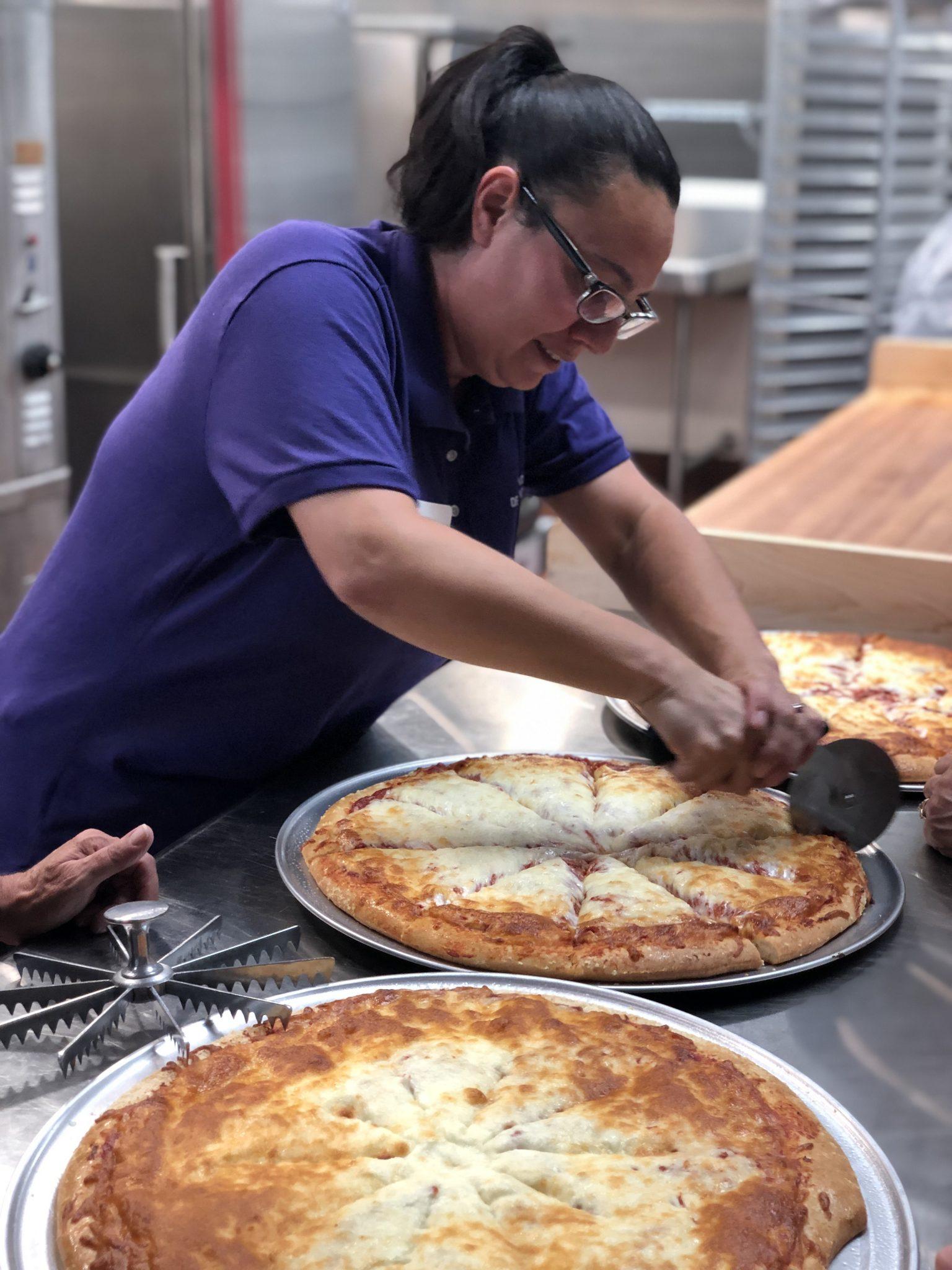A woman cuts a pizza in a school kitchen.