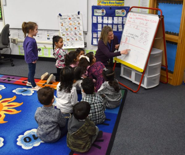 A teacher writes on an easel dry erase board while young students sitting on the floor watch.