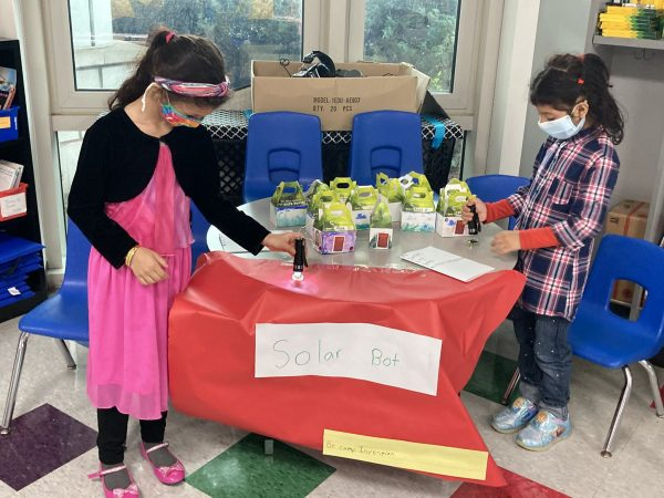 Two girls in face masks do a hands-on activity at a school table.